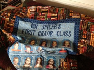 A gift from grateful parents: a quilt featuring a border of books and the names and photos of the students.