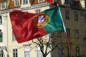 A Portuguese flag flaps in the wind at the end of the march in Rossio Square.