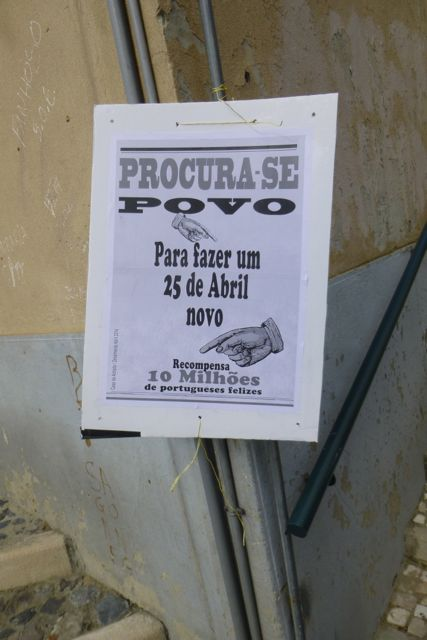 """A sign posted throughout downtown Lisbon reads, """"Wanted: People to make a new April 25. Salary: 10 million happy Portuguese."""""""