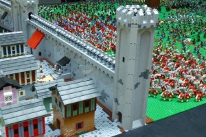 An invading army gathers outside the castle gates while the townspeople go about their business.