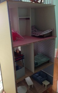 The interior of the dollhouse, with wallpaper, chair rails, and other period details.